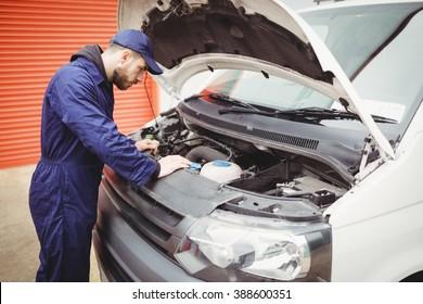 Mechanic fixing the engine of a van