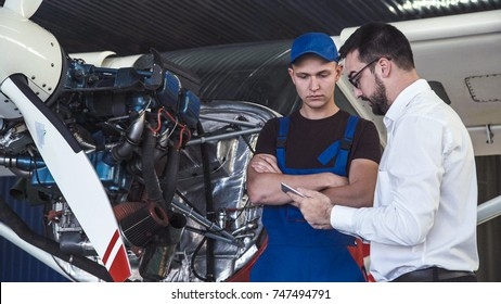 Mechanic and flight engineer having a discussion looking at a tablet-pc together as they stand in front of a small single engine aircraft in a hangar.