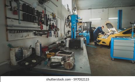 Mechanic In The Garage, Car Preparing For Repairing, Wide Angle
