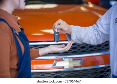 Mechanic give car key to customer after finished fix car. After Sale Service Chevrolet-Lao at Vientiane Capital, Laos. photo were taken on November 9 2016.