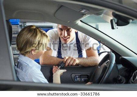 mechanic giving car keys to client sitting in car