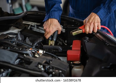 mechanic hand charging battery of a car with electricity through jumper cables