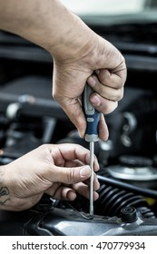Mechanic hand checking and fixing a broken car in car service garage