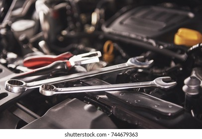 Mechanic hand checking and fixing a broken car in car service garage.