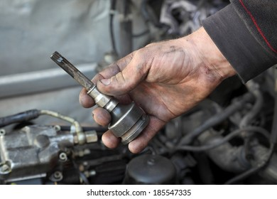 Mechanic hand  hold socket spanner driver  tool in hand with engine in background