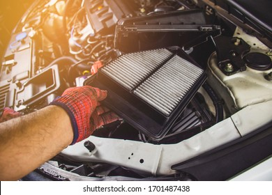 Mechanic hand is replacement car air filter into the filter socket of a car engine,Automotive part concept.