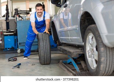mechanic hands in blue uniform pushing a black tyre in a workshop