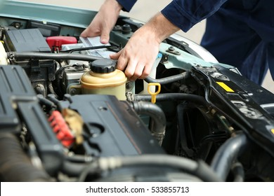 Mechanic hands checking up of serviceability of the car in open hood, close up