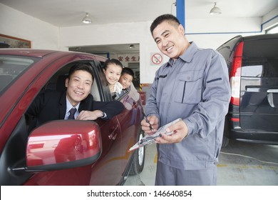 Mechanic Helping Family with Their Car
