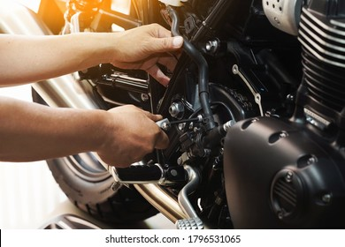 mechanic hold Hex Key Wrench working on motorcycle at motorbike garage , concept of motorcycle maintenance and repair.selective focus