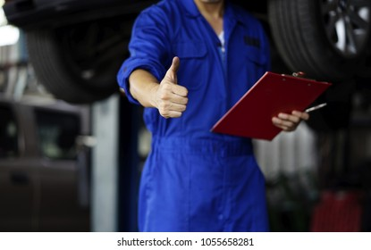 Mechanic holding check sheet on hand to inspection. foreman hold check sheet paper for maintenance. business, maintenance and people concept. Man with clipboard at car repair service or auto store