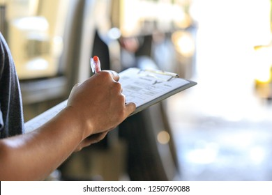 Mechanic holding clipboard with checking truck in service center,