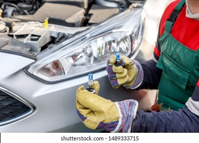 Mechanic holding lamp and cables from headlamp of car