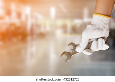 Mechanic holding pair of wrench at car servicing centre