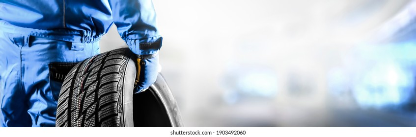 Mechanic holding tire with copy space for text repair service center, blurred background, Maintenance transport  panorama or banner photo.