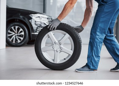 Mechanic holding a tire tire at the repair garage. replacement of winter and summer tires.