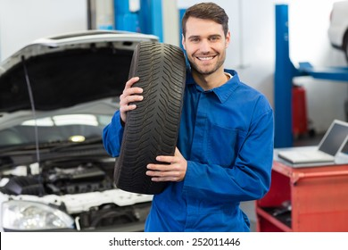Mechanic holding a tire wheel at the repair garage