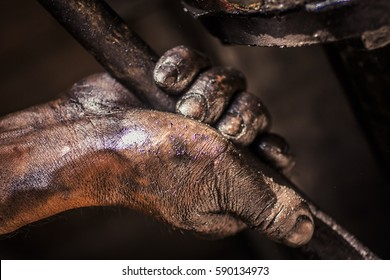 Mechanic holding a tool with grease on his hand