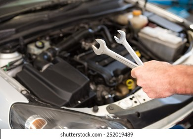 Mechanic holding two types of wrench in the repair garage