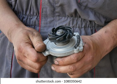 Mechanic holding water pump for car with sealing paste added