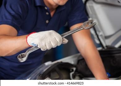 Mechanic Holding Wrench While Examining Car Engine