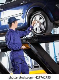 Mechanic Inflating Car Tire At Garage