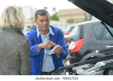 mechanic inspecting the oil of the car