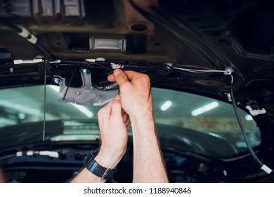 Mechanic installing car central door lock motor.
