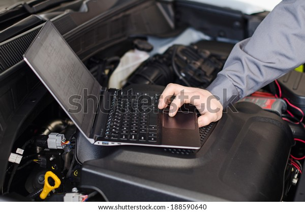 Mechanik mit Laptop-Diagnose Auto in der Werkstatt.