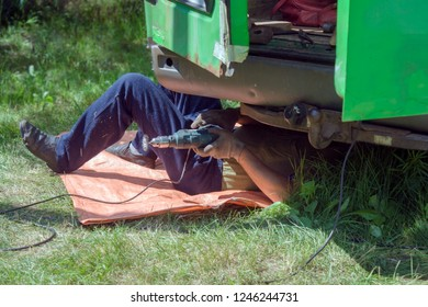The mechanic lies under the car and repairs the body of a green minibus in the summer on the green grass outside.