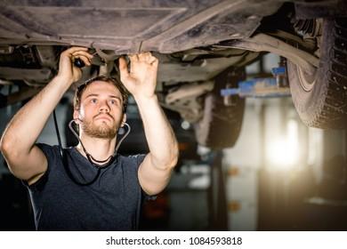 mechanic listen engine with stethoscope in repair garage