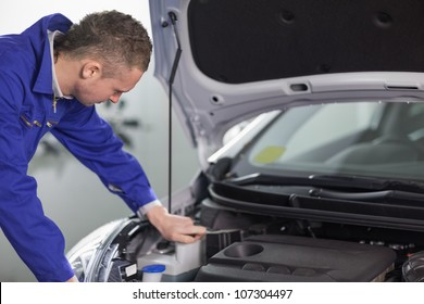 Mechanic looking at an engine while leaning on it in a garage