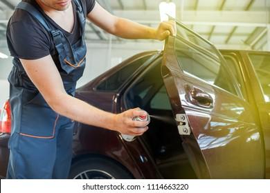 Mechanic lubricates the car, repairs the car door, lubrication spray