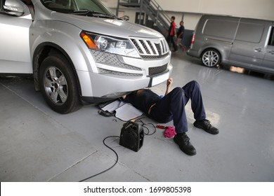 Mechanic lying and working under car at the repair garage workshop