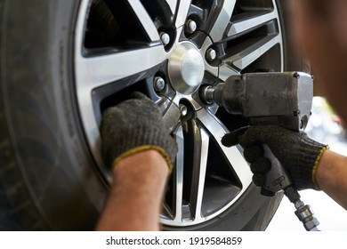 Mechanic male use air gun try to remove nut wheel for replace tires in car service garage