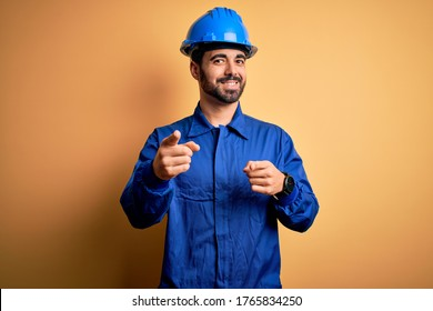 Mechanic man with beard wearing blue uniform and safety helmet over yellow background pointing fingers to camera with happy and funny face. Good energy and vibes.