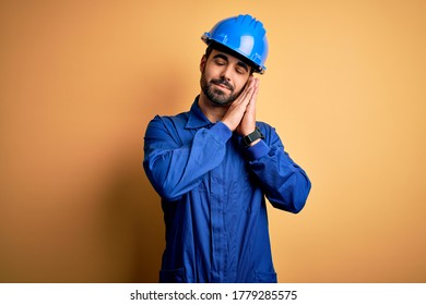 Mechanic man with beard wearing blue uniform and safety helmet over yellow background sleeping tired dreaming and posing with hands together while smiling with closed eyes.