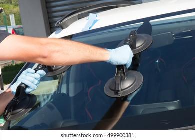 Mechanic man is changing windscrenn on a car