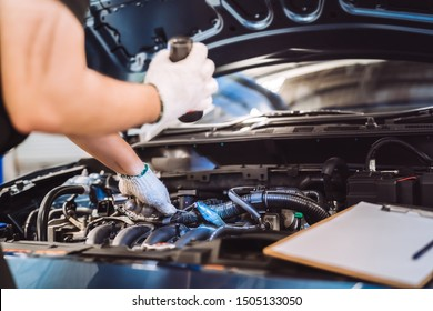 Mechanic man examining and maintenance to customer the engine a vehicle car hood, Safety inspection test engine before customer drive on a long journey, transportation repair service center