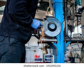 Mechanic man in his workshop with blue suit polishing a part in the polishing machine and sparkles and sparks come out