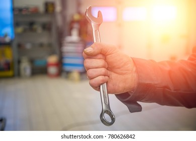 Mechanic man is holding a combination wrench in his hand.