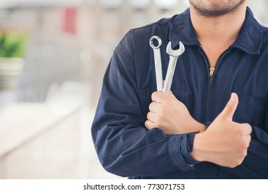 Mechanic Man holding wrench and thumbs up. Auto repair garage.