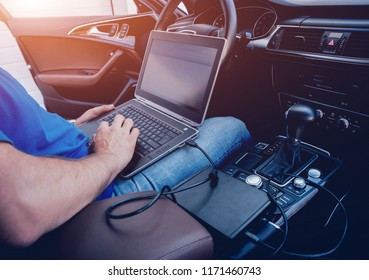 Mechanic man with laptop making car diagnostics at auto service. Background