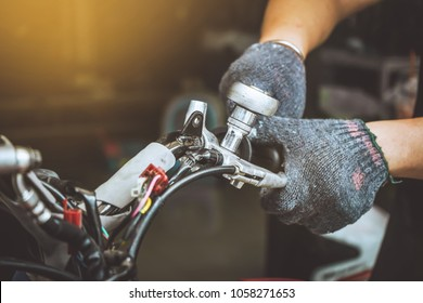 Mechanic man using a wrench to Repair or maintain motorcycle at motorcycle shop , selective focus