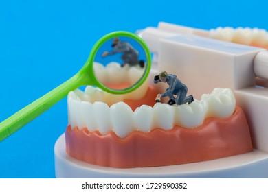 Mechanisches Modell Miniatur Menschen reinigen Zahnmodell als medizinisches und medizinisches Konzept, regelmäßige Kontrollen sind von wesentlicher Bedeutung für die Mundgesundheit auf blauem Hintergrund. Konzept: Medizin und Gesundheitswesen, Menschen