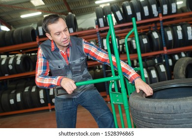 a mechanic moving heavy tyres