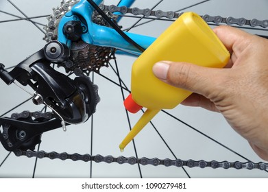 Mechanic oiling bicycle chain and gear with oil. Studio shot