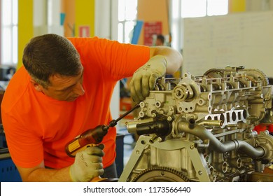 The mechanic in the orange jersey installs the camshaft position sensor on the cylinder head of the engine.