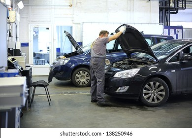Mechanic in overalls opened hood of black car in small service station.