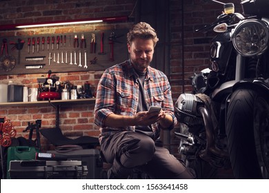 Mechanic pausing to read a message on his mobile phone as he kneels alongside a vintage motorcycle that he is repairing or servicing in a workshop